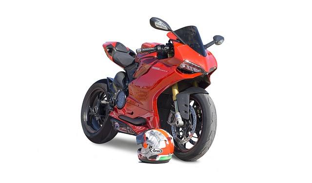 helma ležící vedle červené motorky